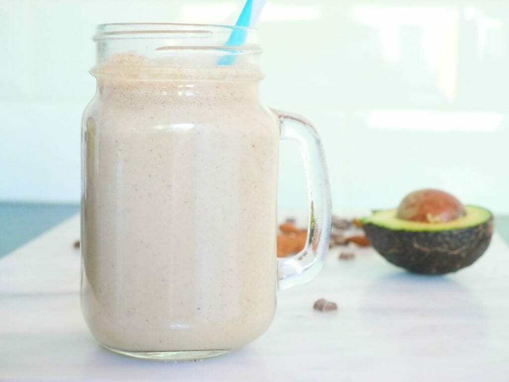 A hero shot of a chocolate almond butter smoothie with coconut and protein