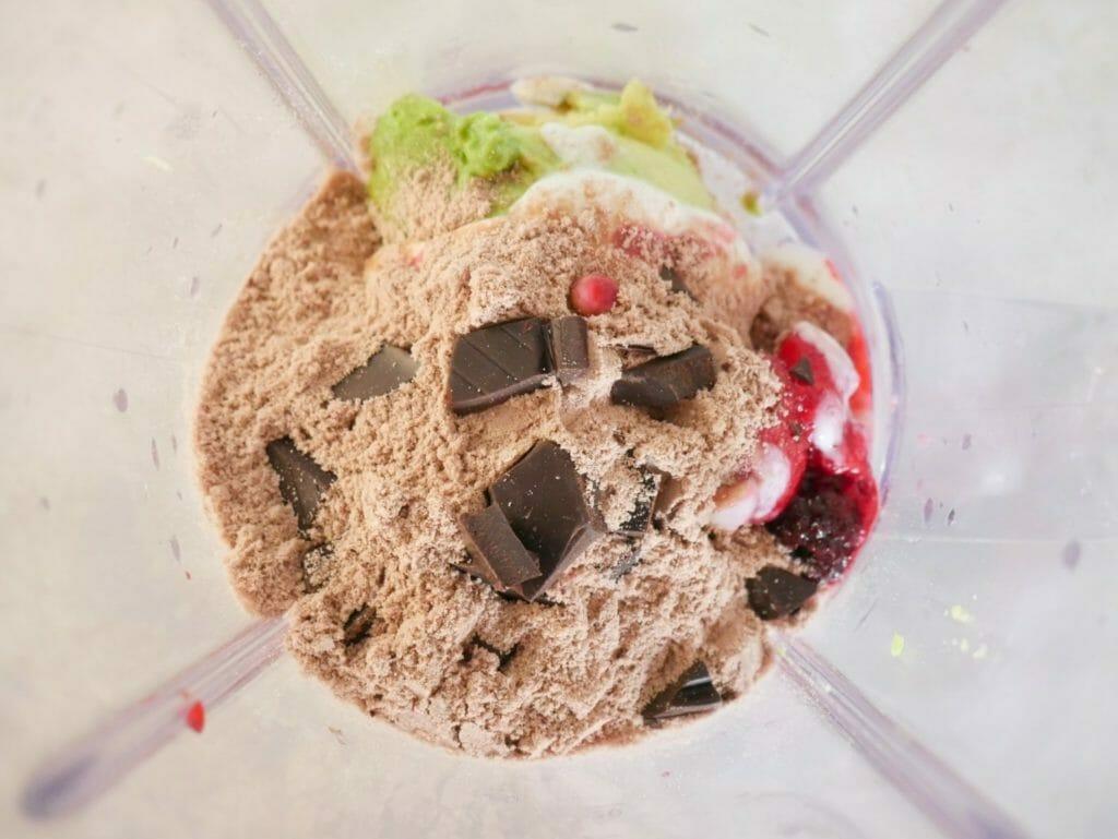 Ingredients in a blender - chocolate chunks, chocolate protein powder, avocado, mixed berries, yogurt