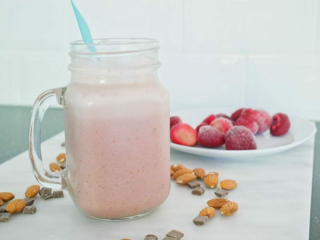 Strawberry chocolate protein shake with strawberries behind and almonds scattered around it