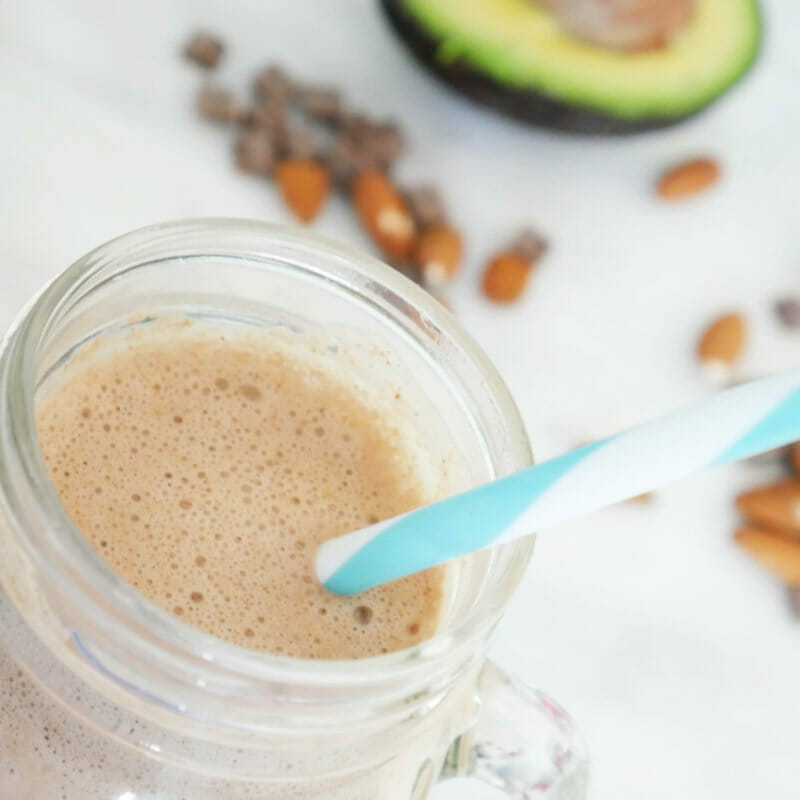 Protein shakes smoothies with avocado, almonds, chocolate in the background and a white and blue straw